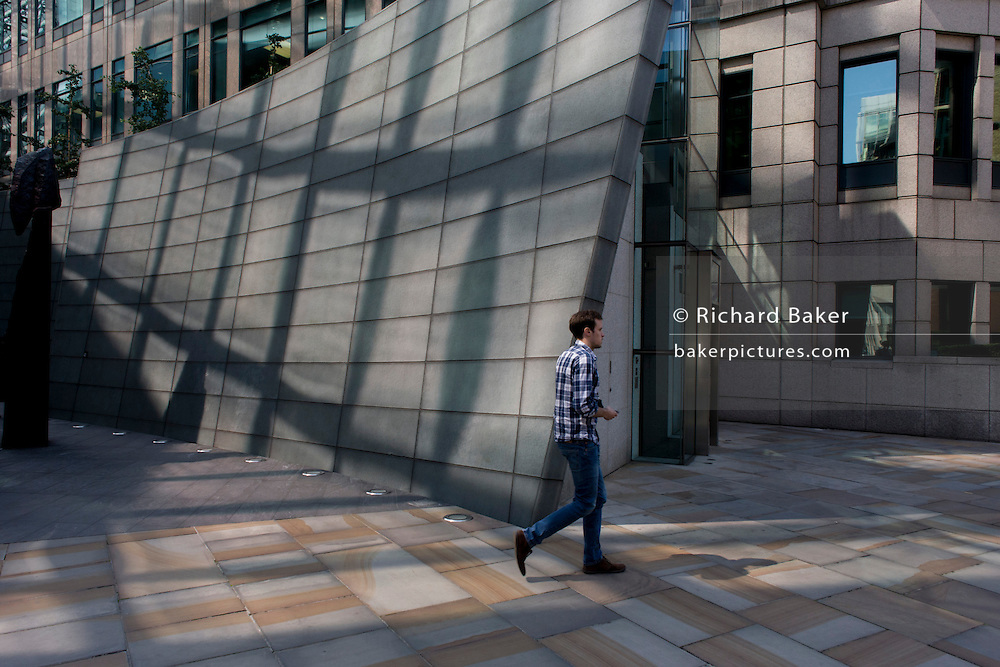 1980s architecture at the Broadgate City of London development and matching design of chequered shirt man.
