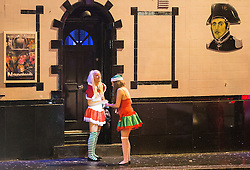 """© Licensed to London News Pictures . 20/12/2014 . Manchester , UK . Two women dressed in seasonal costumes outside Napoleons pub on Bloom Street . """" Mad Friday """" revellers out in the rain and cold in Manchester . Mad Friday is typically the busiest day of the year for emergency services , taking place on the last Friday before Christmas when office Christmas parties and Christmas revellers enjoy a night out .  Photo credit : Joel Goodman/LNP"""