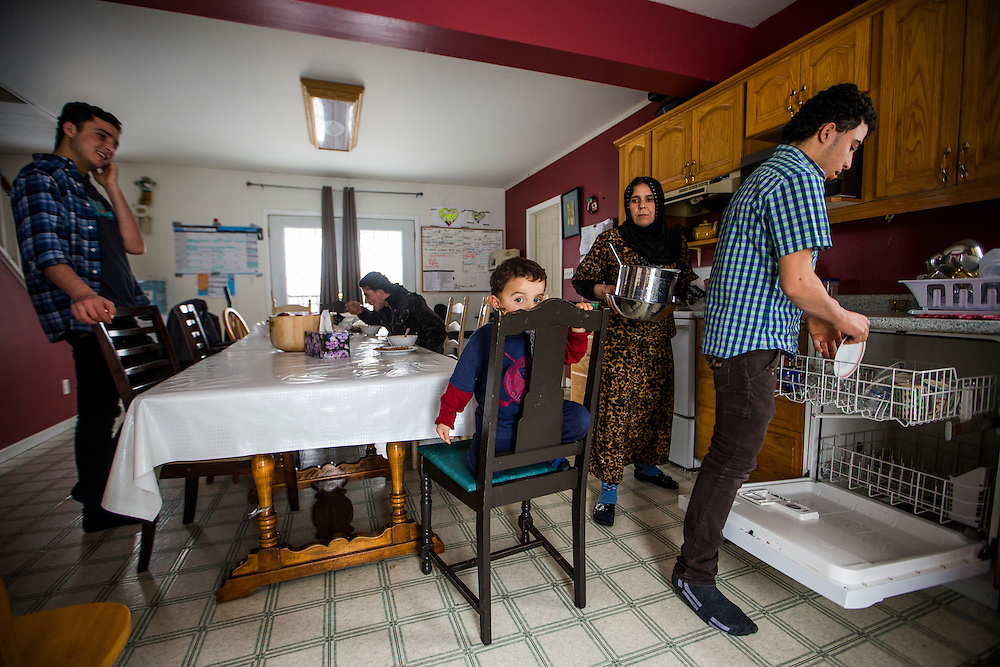 Syrian refugee Fadl Al Jasem (centre), sits on a chair as his mother Sawsan (second right), brother Ahmad (right), brother Ramaz (left), and brother Sleiman Abdel Malek (back), use the kitchen inside their temporary home in Picton, Ontario, Canada, Wednesday January 20, 2016.   (Mark Blinch for the BBC)