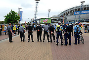 A line of railway security guards and policemen watch the 2008 Rugby League Grand Final on a big screen set up outside the Olympic Stadium. Sydney, Australia