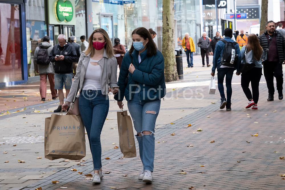 With new local coronavirus lockdown measures now in place and Birmingham currently set at 'Tier 2' or 'high', people wearing face masks continue to go shopping in the city centre on 14th October 2020 in Birmingham, United Kingdom. This is the first day of the new three tier system in the UK which has levels: 'medium', which includes the rule of six, 'high', which will cover most areas under current restrictions; and 'very high' for those areas with particularly high case numbers. Meanwhile there have been calls by politicians for a 'circuit breaker' complete lockdown to be announced to help the growing spread of the Covid-19 virus.