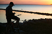 A you man is catching Pokemons in the setting sun by the sea near the citadel in Landskrona, Sweden, 27th of August 2016.