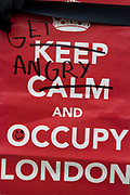 "Keep Calm and Carry of spoof. Occupy London protest at St Pauls, October 16th 2011. Protest spreads from the US with this demonstrations in London and other cities worldwide. The 'Occupy' movement is spreading via social media. After four weeks of focus on the Wall Street protest, the campaign against the global banking industry started in the UK this weekend, with the biggest event aiming to ""occupy"" the London Stock Exchange. The protests have been organised on social media pages that between them have picked up more than 15,000 followers. Campaigners gathered outside  at midday before marching the short distance to Paternoster Square, home of the Stock Exchange and other banks.It is one of a series of events planned around the UK as part of a global day of action, with 800-plus protests promised so far worldwide.Paternoster Square is a private development, giving police more powers to not allow protesters or activists inside."