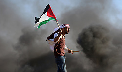 June 16, 2017 - Gaza City, Gaza Strip, Palestinian Territory - A Palestinian protester waves the national during clashes with Israeli security forces following a protest near the border fence east of Jabalia refugee camp, against the blockade on the Gaza Strip on June 16, 2017  (Credit Image: © Yasser Qudih/APA Images via ZUMA Wire)