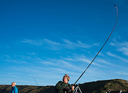 © Licensed to London News Pictures. <br /> 12/10/2014. <br /> <br /> Saltburn, United Kingdom<br /> <br /> A fisherman reels his line in as he takes part in the annual Jim Maidens memorial beach fishing competition in Saltburn by the Sea in Cleveland. <br /> The competition is held each year to mark the death of Saltburn plumber and keen fisherman Jim Maidens who died in 1998 when he was killed after being swept overboard from his boat 'Corina' close to the beach at Saltburn.<br /> <br /> Photo credit : Ian Forsyth/LNP