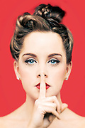 Studio photograph of young woman with a finger held against her mouth making a 'quiet please' sign. Shot against a red background in a Bristol studio by Jonathan Bowcott