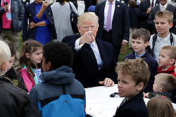 WASHINGTON, DC - APRIL 02: (AFP OUT) U.S. President Donald Trump (C) points to members of the news media while writing messages to military troops during the 140th annual Easter Egg Roll on the South Lawn of the White House April 2, 2018 in Washington, DC. The White House said they are expecting 30,000 children and adults to participate in the annual tradition of rolling colored eggs down the White House lawn that was started by President Rutherford B. Hayes in 1878. (Photo by Chip Somodevilla/Getty Images)