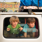Two boys watch out of a window from a camping car.