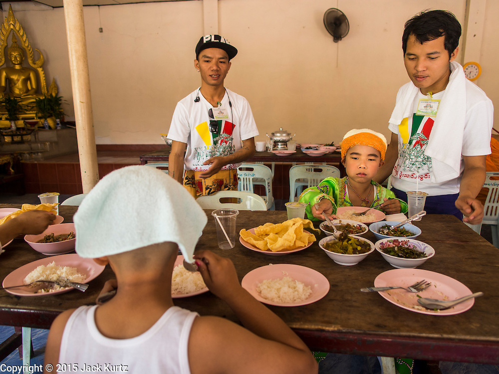 """04 APRIL 2015 - CHIANG MAI, CHIANG MAI, THAILAND:  Boys being ordained as Buddhist novices eat their lunch at the Poi Sang Long Festival at Wat Pa Pao in Chiang Mai. The Poi Sang Long Festival (also called Poy Sang Long) is an ordination ceremony for Tai (also and commonly called Shan, though they prefer Tai) boys in the Shan State of Myanmar (Burma) and in Shan communities in western Thailand. Most Tai boys go into the monastery as novice monks at some point between the ages of seven and fourteen. This year seven boys were ordained at the Poi Sang Long ceremony at Wat Pa Pao in Chiang Mai. Poy Song Long is Tai (Shan) for """"Festival of the Jewel (or Crystal) Sons.     PHOTO BY JACK KURTZ"""