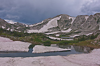 Snow melting away from one of the many lakes of the Snowy Range of the Medicine Bow Mountains.   Snowbanks in the Snowy Range harbor thriving communties of microspic organisms in late summer.  The pinkish tinge is caused by algae which also contain the chemical anthocyanin.  Wyoming.