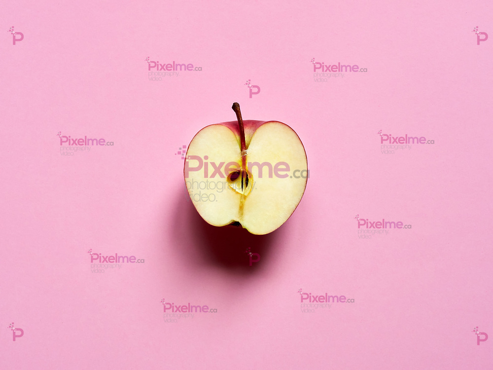 Apple fruit sliced by half isolated in studio over a light pink background