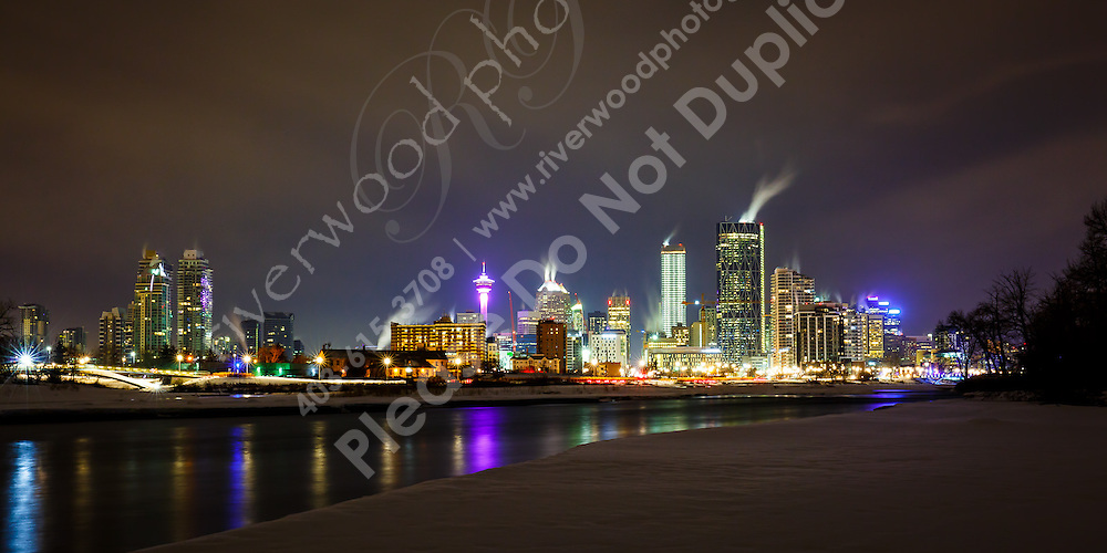The Calgary skyline and the Bow River at night in winter, as seen from St. Patricks Island in East Calgary.<br /> <br /> ©2017, Sean Phillips<br /> http://www.RiverwoodPhotography.com