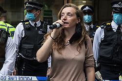 Tree protector 'Swan' addresses fellow activists from HS2 Rebellion, an umbrella campaign group comprising longstanding campaigners against the HS2 high-speed rail link as well as Extinction Rebellion activists, at a protest outside the Department for Transport on 4 September 2020 in London, United Kingdom. Activists glued themselves to the doors and pavement outside the building and sprayed fake blood around the entrance during a protest which coincided with an announcement by HS2 Ltd that construction of the controversial £106bn high-speed rail link will now commence.