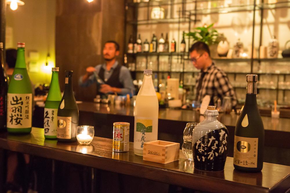 Bottles of sake and shochu on display in the bar area at SakaMai.