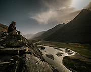 On his way home, under moonlight, a teenager takes a break high above the Wakhan river . The traditional life of the Wakhi people, in the Wakhan corridor, amongst the Pamir mountains.