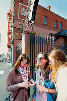 Three young women stop to check phone directions by Market Square on lower Johnson Street while shopping in downtown Victoria, BC