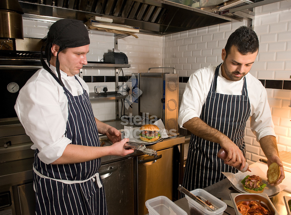 Picture by Daniel Hambury. .9/12/11.Chef/owner Alberto Figueroa (right) and line chef Peter Hrin prepare burgers in the kitchen of Bukowski Grill in Shoreditch, east London.