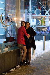 """© under license to London News Pictures. 18/12/2010 as snow blizzards hit Manchester revellers continue their """"Mad Friday"""" night out. These girls shelter from the snow but cannot escape the cold"""