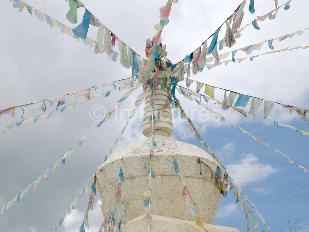 A stupa (or chorten in Tibetan), Tangu village, Yunnan province, China. Stupas are important religious monuments for Tibetans. This unique religious architectural form expresses significant religious symbolism and presents Buddha's physical presence. It generally consists of three parts; a whitewashed base, a whitewashed cylinder and a crowning steeple or shaft. Tibetans perform their  prayers several times a day whilst circulating the stupa.