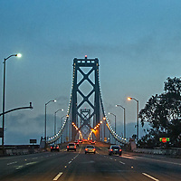 Cars rush across the Bay Bridge, approaching San Francisco, California, that is disappearing into a fog bank.