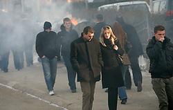 PRISTINA, KOSOVO - DECEMBER 14 - ljudje na plocniku hodijo mimo gorecega smetnjaka