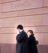 two business people walking past lovels office in london