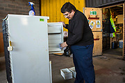 A member of staff cleaning a donated secondhand fridge freezer ready to pass onto someone in need. Longton Community Church work to improve the lives of those in need in their local community, Leyland, Lancashire.