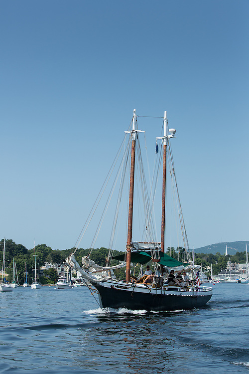 Camden, ME - 11 August 2014. The windjammer schooner Mistress motoring out of Camden with tourists on deck.