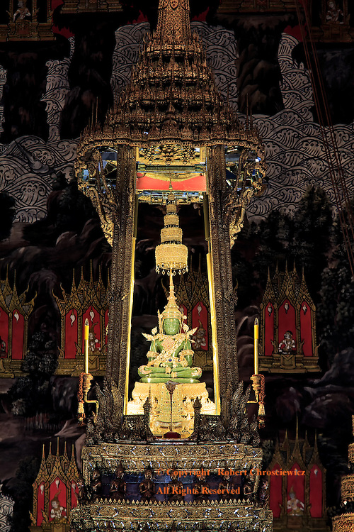 Emerald Buddha: An intricately decorated Phra Mondop ( temple of the Emerald Buddha) with a bejewelled Emerald Buddha, surrounded by ornate depictions of heaven people, demons and buildings is on display on its golden throne in the Thai Imperial Grand Palace, Bangkok Thailand.