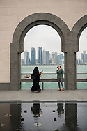 An Arab woman walks while looking at her mobile phone while another woman, visiting from Uzbekistan, takes a selfie outside the Islamic Musueum of Art in Doha, Qatar.
