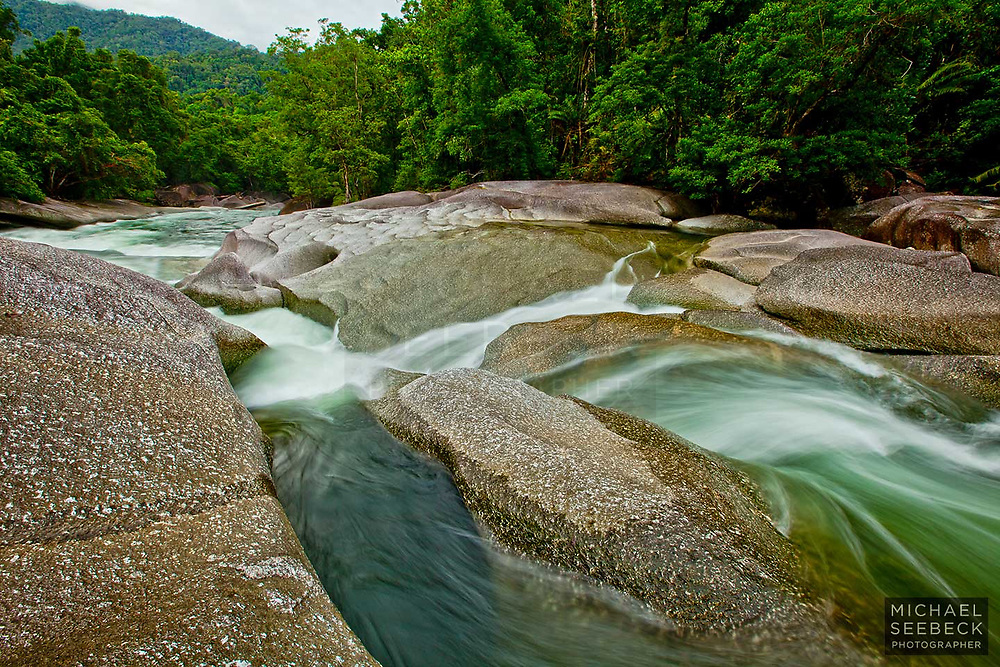 Clear water from the Mt Bellenden Kerr rainforest surges over a waterfall at the Babinda Boulders.<br /> <br /> Open Edition Print / Stock Image
