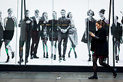 A pre-Christmas shopper walks past a video ad loop for the London retailer Reserved, on Oxford Street, on 22nd November 2017, in London England.