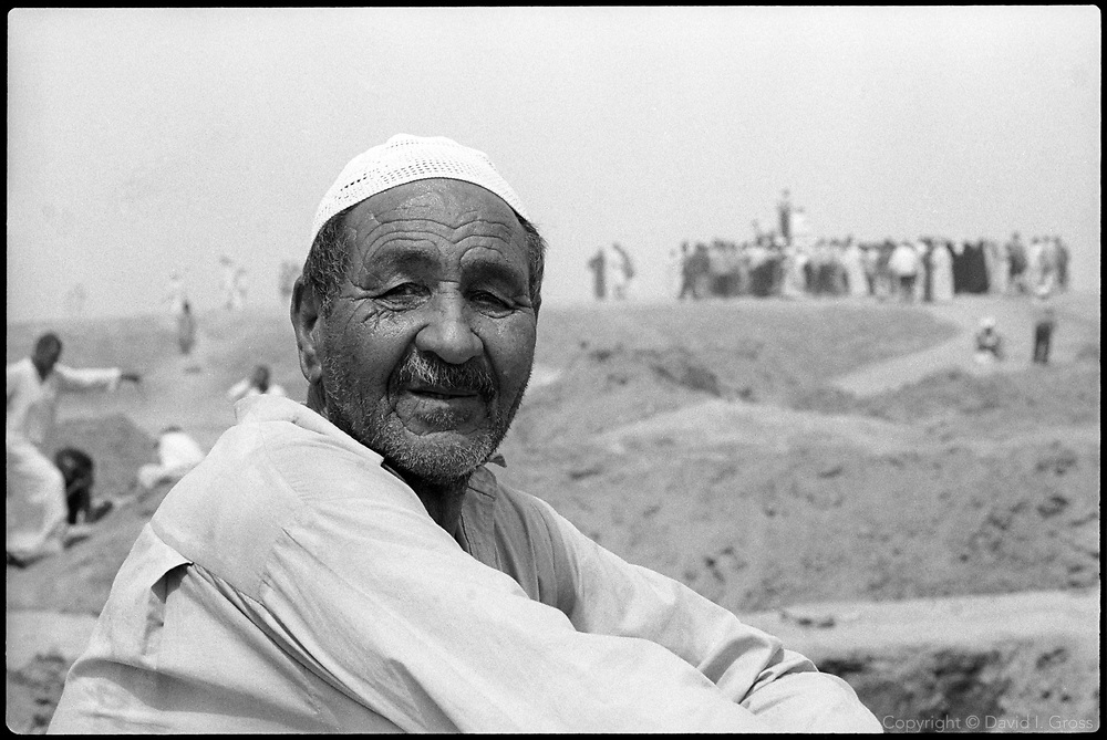 An Iraqi man smiles for the camera at a mass grave site near Hillah, Iraq.
