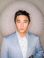 Headshot of asian man (40-45 years old) listening to mp3 player with earbuds