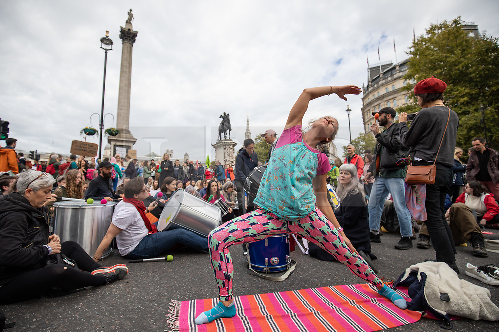 © Licensed to London News Pictures. 07/10/2019. London, UK. A climate change activist performs yoga as part of a stage a sit down demonstration in Trafalgar Square, London, closing the road to traffic, as part of a wider two week long demonstration to cause disruption in the capital. The activists are calling for the government to acknowledge and act on climate change. Photo credit : Tom Nicholson/LNP