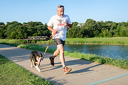 Jogger and dog on the Trinity Trails near the Trinity River, Fort Worth, Texas, USA.