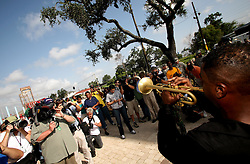 29 August 2006. Lower 9th Ward. New Orleans, Louisiana. Lower 9th ward. Great Flood commemoration and memorial ceremony; to 'honor and remember our loved ones who have passed. <br /> Surrounded by the media, world renowned jazz trumpeter Marlon Jordan gives a salute to the dead at the newly erected memorial to victims of hurricane Katrina, which strick one year ago today.<br /> Photo Credit©; Charlie Varley/varleypix.com