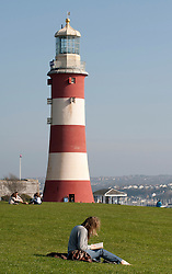 © under license to London News Pictures.  15/03/2011 A student reads a book in front of the lighthouse on Plymouth Hoe and enjoys the Spring sunshine and warm weather in Plymouth, Devon. Picture credit sould read: David Hedges/LNP