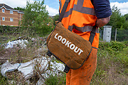 Lookout written on a bag held by a man dressed in high-visibility work clothes on 17th June 2019 in Aldershot Railway Station, Hampshire, United Kingdom.
