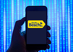 Person holding smart phone with   On the Beach online travel booking website   logo displayed on the screen. EDITORIAL USE ONLY