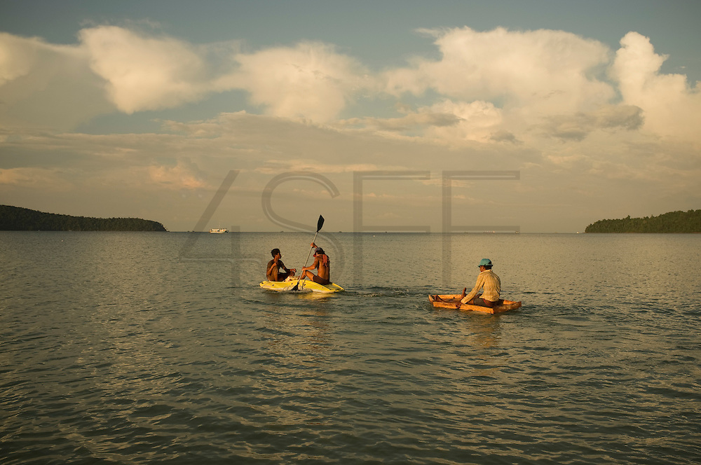 Two man in a canoe pool another one in a raft, Koh Rong Island, Kingdom of Cambodia. PHOTO TIAGO MIRANDA