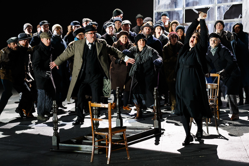"""LONDON, UK, 21 June, 2016. Graeme Danby (foreground left in tweed coat, as Mayor) and Michaela Martens (foreground right, with knife, as Kostelnicka Buryja) rehearse with members of the cast for the revival of director David Alden's production of Janacek's opera """"Jenufa"""" at the London Coliseum for the English National Opera. The production opens on 23 June. Photo credit: Scott Rylander."""