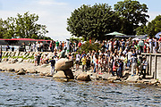 Copenhagen, Denmark. A crowd of tourists photographing the famous statue of the Little Mermaid