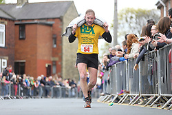 © Licensed to London News Pictures. 17/04/2017. Gawthorpe UK. Competitors take part in the mens race of The World Coal Carrying Championships in the village of Gawthorpe in Yorkshire. Every year Men & women carry huge sacks of coal from the Royal Oak Pub in Ossett 1012 metres to the finish line at the Maypole Green in the village of Gawthorpe. Photo credit: Andrew McCaren/LNP