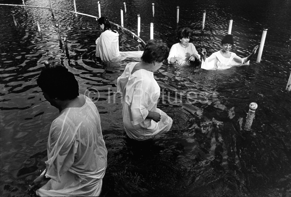 Pilgrims being baptised in the River Jordan, Kibbutz Kinneret, Israel.Some half a million pilgrims and tourists come to be baptised in the waters that Jesus was baptised by John the Baptist.