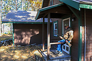 """Dave Evenson sits on the front landing at the """"Big Red Cabin on the Hill"""" made famous in several Old Duck Hunters Association stories by Gordon MacQuarrie in the 1930s. Sometime after MacQuarrie's time, owner Joe Hollis cut the cabin in half, painted it brown and moved one half to another location. This cabin sits very near it's original site overlooking Nancy Lake and Deep Lake."""