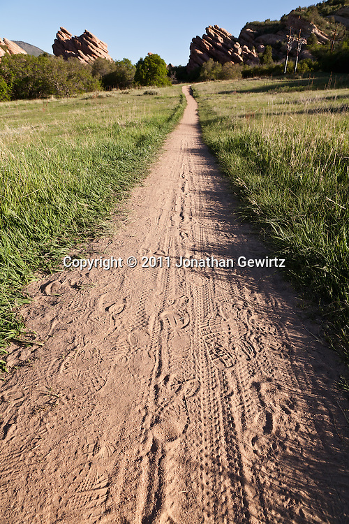 A hiking and biking path runs between protruding red rock strata in the South Valley Park Ken-Caryl Ranch Open Space in Colorado. WATERMARKS WILL NOT APPEAR ON PRINTS OR LICENSED IMAGES.
