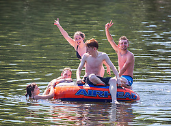 © Licensed to London News Pictures. 25/06/2020. London, UK. Young people prank about on the River Thames at Richmond in South West London as forecasters predict the hottest day of the year so far with temperatures expected to reach 33c. Prime Minister, Boris Johnson announces this week that tourism and hospitality, including pubs, restaurants and campsites can now reopen from the 4th of July as well as reducing the 2 metre rule to 1 metre. Photo credit: Alex Lentati/LNP