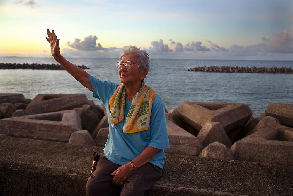 Masako Taira, 90, waves as the sun sets in Ogimi, Okinawa.