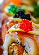 Tsubaki sushi's Las Vegas roll with spicy crab, avocado, deep fried tuna and topped with yellowtail, lemon slice, and eel sauce.
